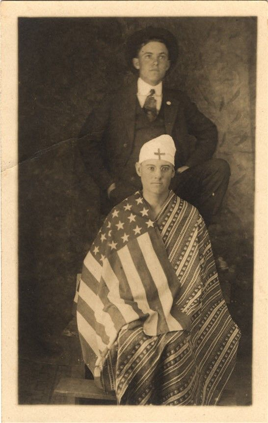 A male missionary nurse sits wrapped in the American flag and a traditional indigenous blanket, United States, ca. 1910. Pictures of Nursing: The Zwerdling Postcard Collection. National Library of Medicine