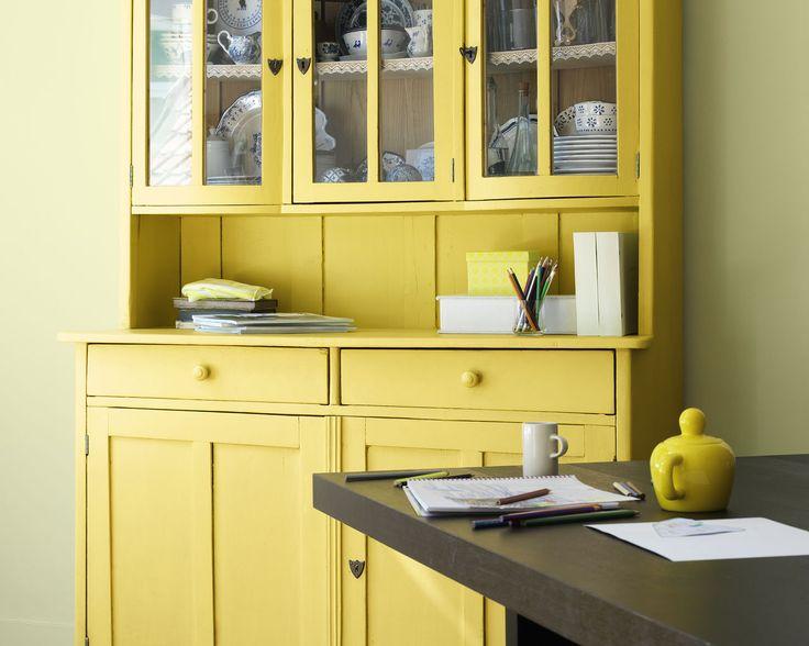 Ensoleillez votre salle à manger ! Ce buffet de cuisine traditionnel peint en jaune vif ressort devant le mur d'un vert acidulé et frais.