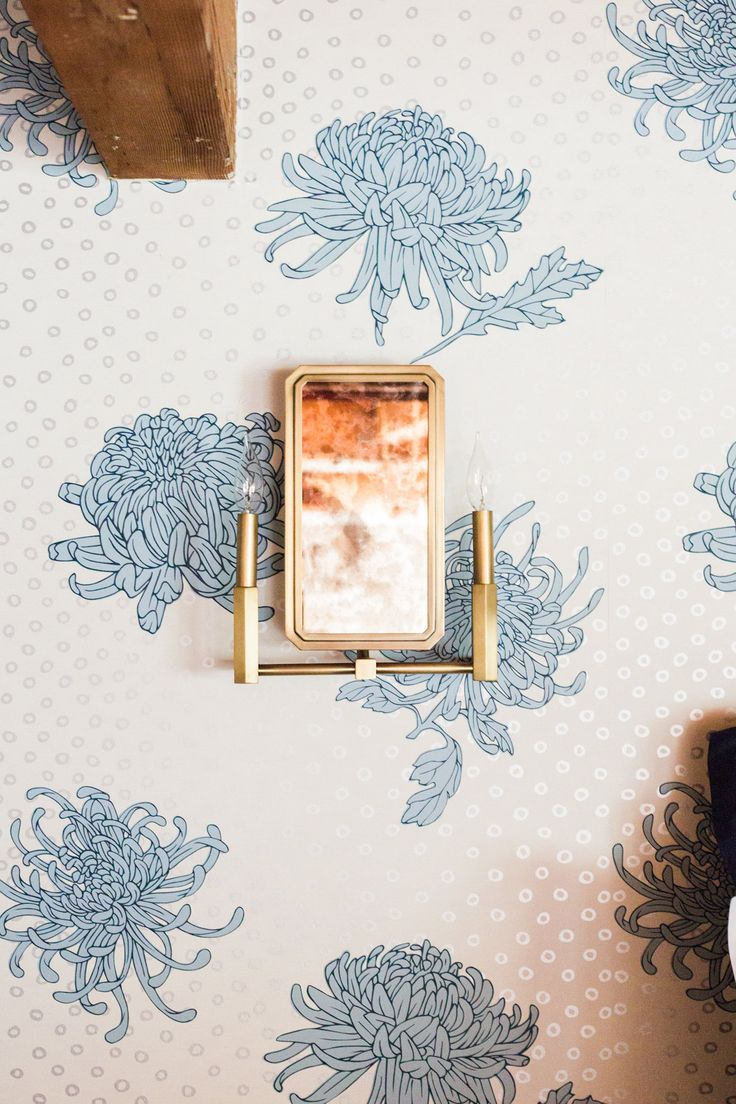 Beautiful gold bedroom sconce lighting + funky wallpaper.