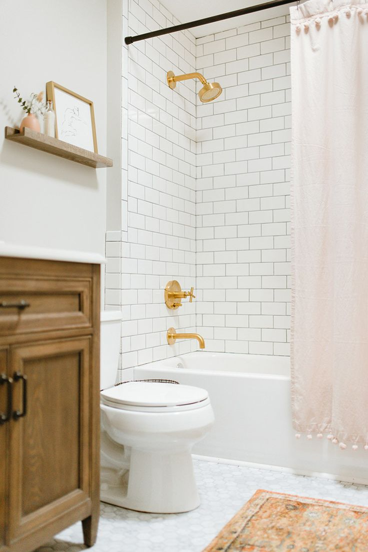 A gorgeous natural wood vanity and eclectic orange rug from the Home Decorators Collection along with matte brushed gold faucet and shower head brings rich color to an otherwise neutral and modern bathroom remodel.