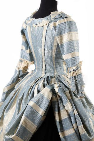 A blue & cream silk polonaise dress, circa 1770s. Of pale blue and cream striped and floral damask silk, elbow length sleeves with altered sleeve frills
