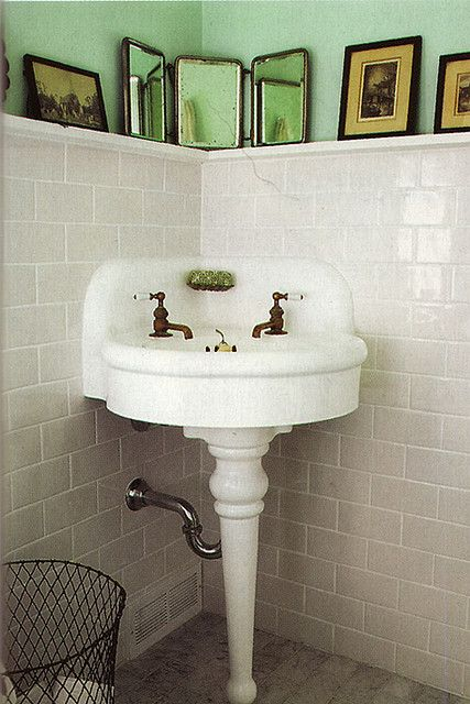 love that green, and the frames on the ledge, also the vintage sink and subway tile