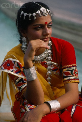 An Indian woman wears traditional dress, including a headdress and jewelry | © Charles & Josette Lenars/Corbis