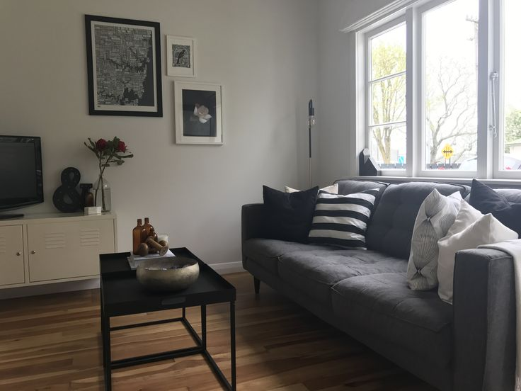 Charcoal sofa, native timber floors, crisp white walls.