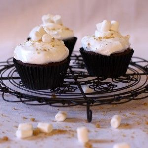 Cupcakes topped with marshmallow frosting on a round wire rack scattered with marshmallows.