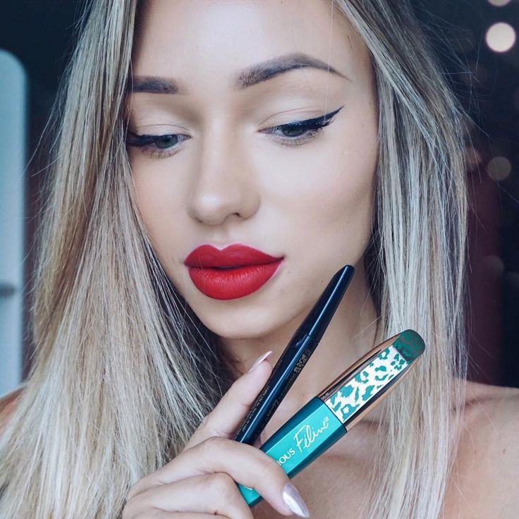 Gorgeous holiday makeup look with a winged cat eye and bold red lip on Liza Lash. Get the look with Voluminous Feline Mascara and Liner Noir.