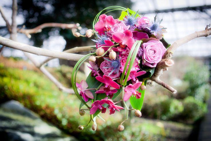 Een bruidsboeket van orchideeen en andere roze en paarse bloemen.