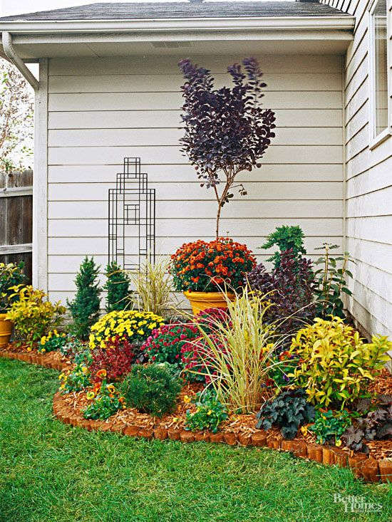 Why it works: The curved edge of the bed softens the 90-degree angle of the corner and creates more visual interest. Hint: Unless you have a formal, geometric garden, incorporate curves as much as you can in your landscape design. They're typically much more pleasing to the eye than straight lines. A series of easy, colorful plants including mums, pansies, spiraea, and purple smokebush makes this border a knockout.