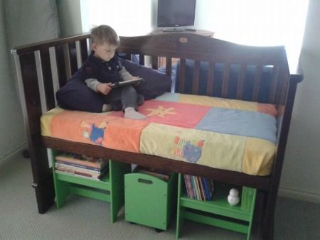 Repurposed baby crib turned into reading nook {featured on Home Storage Solutions 101}