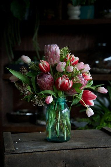 A casual bouquet of tulips and proteas, arranged by Alea Joy of Solabee Flowers and Botanicals