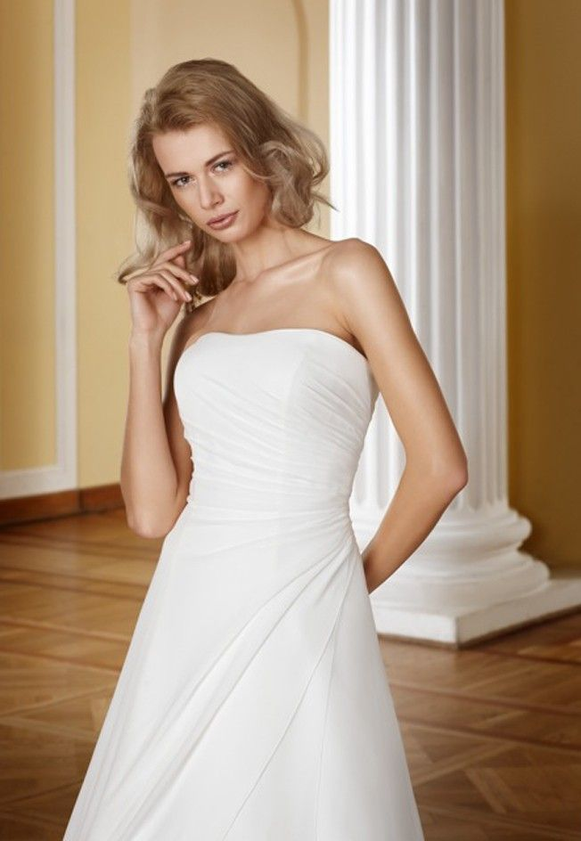 Gepast bij de Bruidshoek. De jurk is egaal en van Saffron. Soort melk achtig wit en heel zacht. Hierdoor zat er een onderrok van zijde onder die de jurk log/zwaar maakte. de rok was niet breed. Dus twijfel over de bijzonderheid van deze jurk. Hij was wel mooi. Maggie Sottero Benta