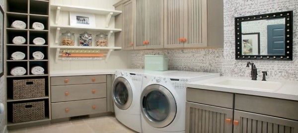 grey and orange laundry room with wooden cabinets for storage - Decoist