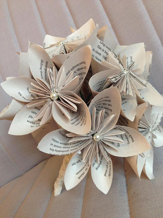 A classic and elegant bouquet, lovingly handmade from the pages of a novel. This paper flower bouquet would look stunning at a literary themed, vintage or shabby-chic wedding.  This flower bouquet is made up of origami kusudama flowers. The flowers are individually handmade and each flower measures approximately 10cm across. A pearl style bead is in the center of each flower. The flower stems are wrapped in vintage lace to give a pretty and comfortable handle. The bouquet itself is very…