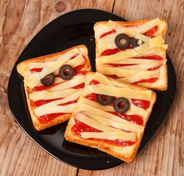 Mummy Toast: Think of these toasts like mini pizzas. Just stick them under the broiler or in the toaster oven to get the cheese nice and melted. (via Spaceships and Laser Beams) | 13 Horrifying + Healthy Halloween Recipes via Brit + Co.