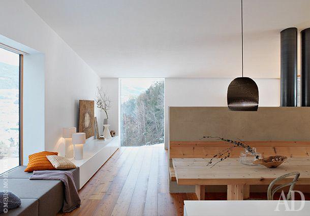 Зона кухни и столовой разделена низкой стеной совстроенным в нее камином. Обеденный стол, Thonet; белые лампы, Ivan Baj for Arcade Avec.