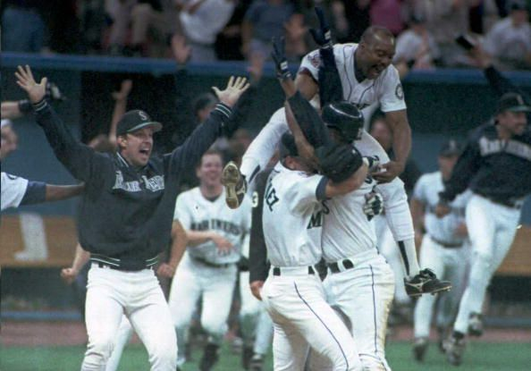 Vince Coleman and his Seattle Mariners teammates celebrate after Edgar Martinez's game winning hit in the 11th inning of their 08 October playoff...