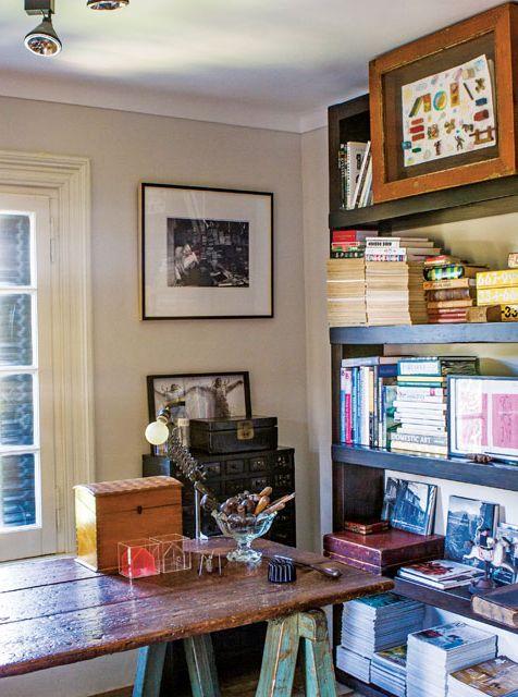 Sector de biblioteca en una casona. Mesa de madera, foto enmarcada con fondo blanco y marco negro, y paredes pintadas en color arena.