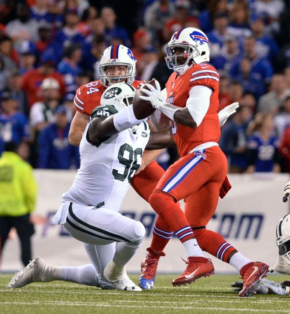 Buffalo Bills quarterback Tyrod Taylor looks to pass under pressure from New York Jets defensive end Muhammad Wilkerson during the first half of an NFL game on Thursday, Sept. 15, 2016, in Orchard Park, N.Y.