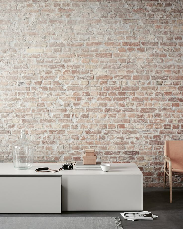 The bulthaup b3 sideboard is also ideal for the living room. In combination with the rough brick wall, the laminate creates a warm and inviting atmosphere.