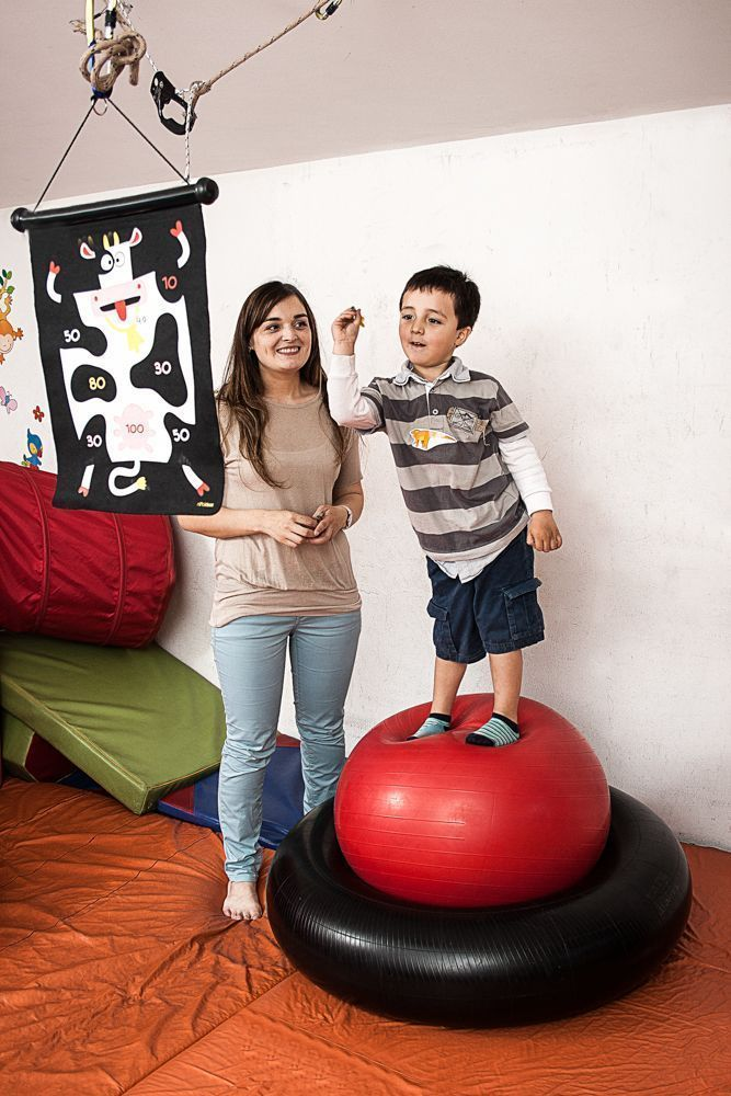 Using an inner tube and a therapy ball in combination to work on dynamic balance. This encourages the child to separate upper and lower limb movement when they are encouraged to throw and catch at the same time.