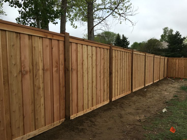 """7' tall cedar privacy fence with 6x6 posts, 2x6 top cap, 6"""" overlapping pickets, and 1x4 top and bottom trim. www.coloradospringsfenceco.com"""