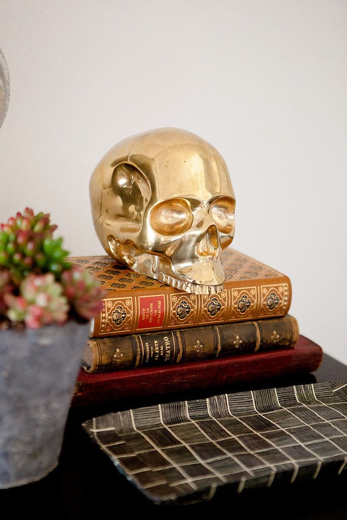Golden skull on top of a stack of vintage books.