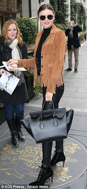 Working it:Miranda added height to her already statuesque frame with a pair of towering lace-up heeled shoe boots, and toted her belongings in an oversized black leather handbag