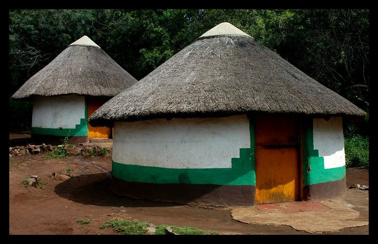 Xhosa huts at the Lesedi Cultural Village.  The Xhosa nation used to build bee-hive shaped huts made of grass, similar to that of the Zulu nation, but with the influence of the early Europeans the huts changed to more permanent conical roofed huts with mud walls. The walls are decorated with whitewash and colorful natural paints.