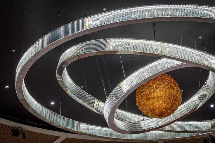 The majestic dome of the Kigali Convention Centre in Rwanda now features an amber sphere created from leaves of hand-blown Bohemian amber glass banked in three rings of 3,5 and 7 meters in diameter. In collaboration Bost Group Berlin and Spacial Solutions from Kigali #light #lighting #design #designlighting #interior #crystal #chandelier #pendant #conference