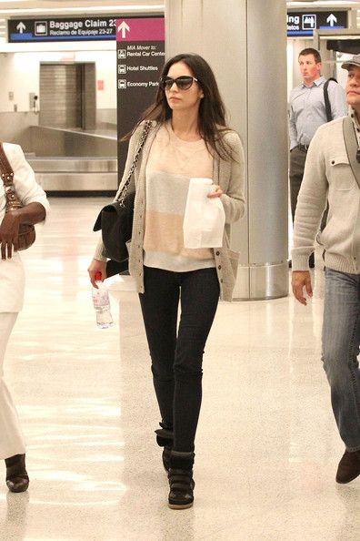 Genesis Rodriguez in a grey sweater, blue skinny jeans and velcro, high top sneakers.