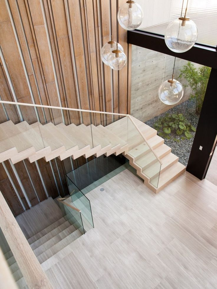 A staircase ascends to the second floor along a wall clad with backlit birch-wood ribbons. The lined panels create continuity with similar striations across the street-facing facade.