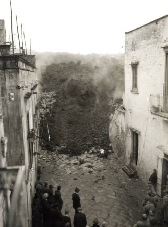Lava flow engulfing a village to the west of Vesuvius, 1944.  Um... why are they all just standing there?!