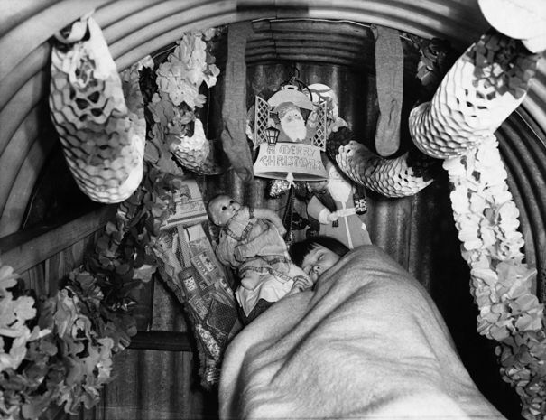 Christmas in an air raid shelter, 1940. This little girl has decorations and presents around her bed.