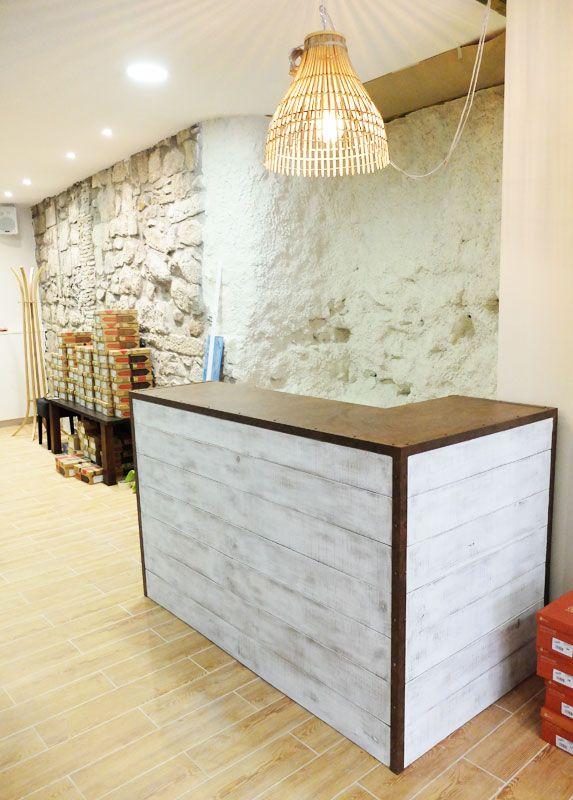 Mostrador a medida con madera en blanco decapado, sobre de chapa y cantoneras con los tornillos vistos y acabado efecto óxido.