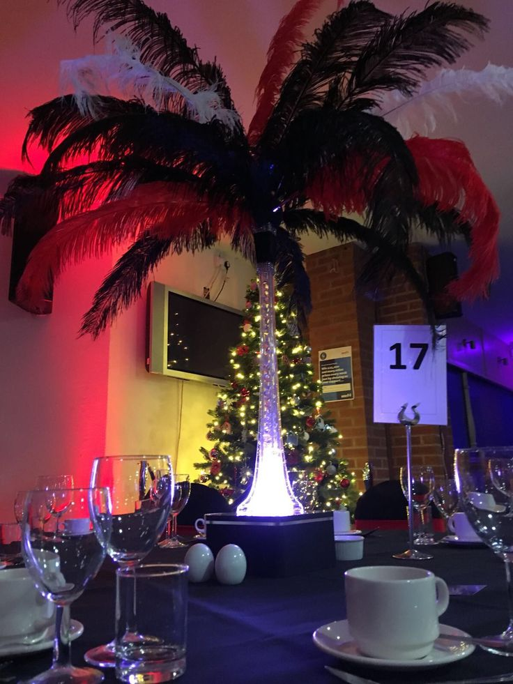 Stunning red, black and white feathered centrepiece in front of the Christmas tree