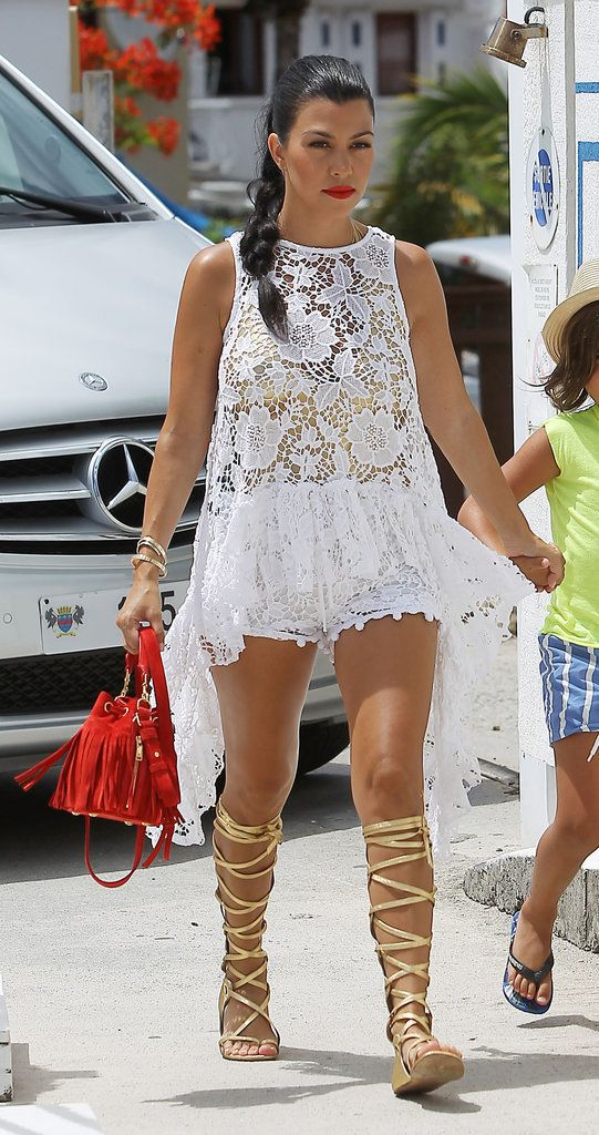 Kardashian Outfits in St. Barts | POPSUGAR Fashion - Kourtney Wore a Lacy See-Through Romper and Knee-High Gladiators She added tomato-red accents with a bright lip and trendy fringe bag.