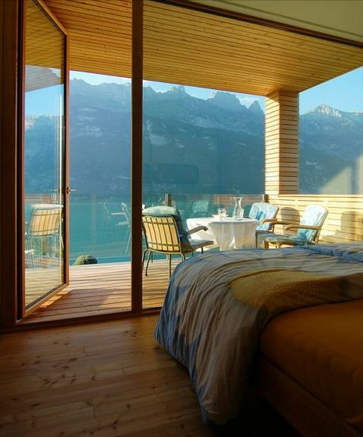 Here is a bedroom with a stunning view combining indoor and outdoor living! Love the hardwood floors and how the wood paneling carries through from inside to out!