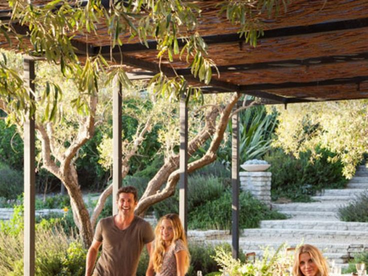 At their residence in Malibu, California, actor Patrick Dempsey and his wife, Jillian, are joined by their children—daughter Talula and sons Darby and Sullivan—and their French bulldog, Horton, in an outdoor dining area appointed with Teak Nichols Design furniture. Conceived by architect Frank Gehry in the late 1960s, the house has been updated with landscaping by Shrader Design and decor by Estee Stanley Interior Design. For details see Sources.