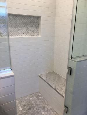 Glass wall in the shower with white subway tiles. …