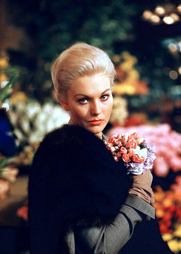Kim Novak. A still from Vertigo (holding Carlota's bouquet),1958.  Edith Head designed her wardrobe, taking the novel decision of putting a blonde in grey (seen here). KA