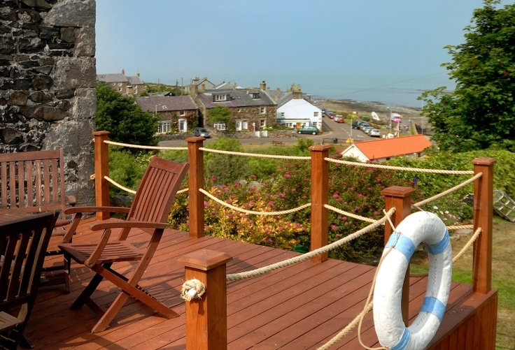 Nautical timber decking with roped fencing, complete with lifebelt, from which to sit and enjoy the coastal views from the end of the secret garden at quirky Coastguard's cottage, Craster