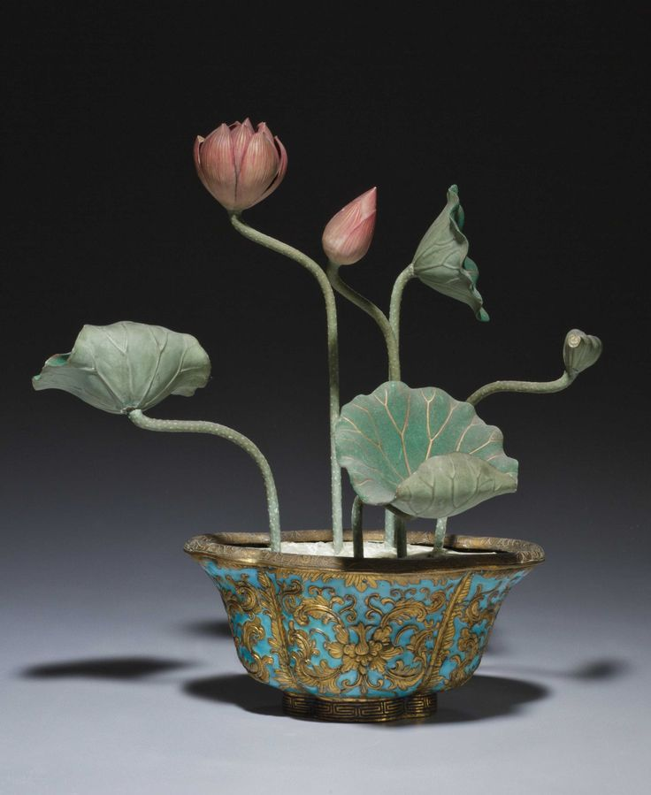 A CHAMPLEVE ENAMEL AND GILT-BRONZE JARDINIERE LATE QING DYNASTY The lobed, quatrefoil-shaped body rests on a conforming foot and is set with a flowering lotus plant. The sides of the vessel are gilt-decorate with floral meander on a turquoise enamel ground.