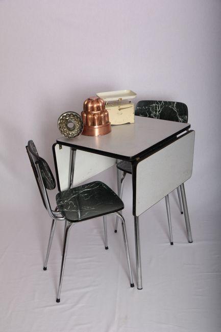 Table en formica blanche/ grise pâle. Pouvant accueillir 4 personnes, elle a l'avantage d'avoir ses côtés rabattables