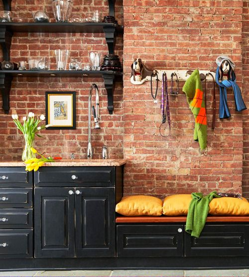 love exposed brick walls paired with the black furniture wiht the pop of orange on the bench!