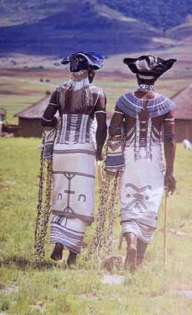 This photograph shows a rear view of two Xhosa men dressed for a tribal dance. Their bead-work is also very elaborate and plentiful, but much more restrained, especially in colour, and they wear the straight cotton cloth kilt of an adult man decorated with black braid appliques. Adult female dress is very similar, but married women wear a very full cotton skirt which is cut on the bias, and cover their breasts with a cloth apron tied around the neck.