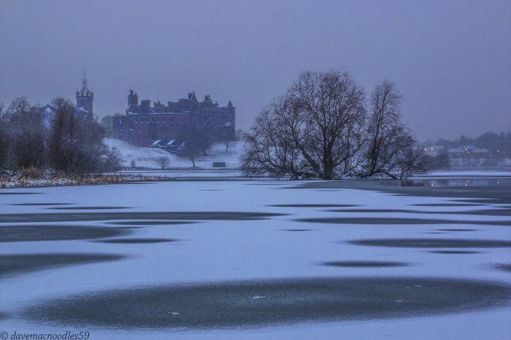 Palace and St. Michael Parish Church across a frozen Loch Linlithgow in West Lothian, Scotland