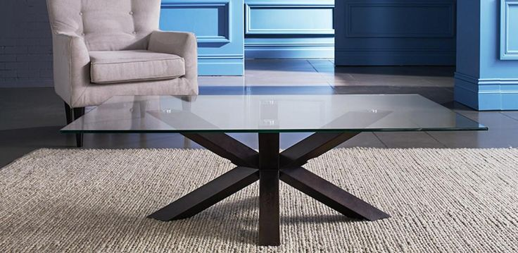 The QUATTRO coffee table has a clear glass top and timber legs in Wenge…