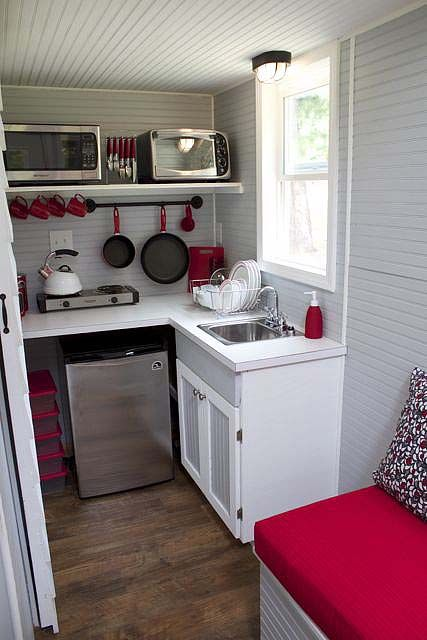 Red and white kitchen from Tennessee Tiny Homes includes hanging pot rack, a hot plate, microwave and...is that a dishwasher?