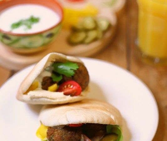 Pita falafel met houmous en rauwkost 8 pitabroodjes 3 eetlepels olie 2 pakken falafelballetjes (à 235 gram per pak) 1 bakje houmous, bijvoorbeeld van Sabra Rauwkost, bijvoorbeeld: ijsbergsla, (cherry) tomaat ,olijven, paprika, rode uienringen, fijngesneden witte kool, verse koriander, plakjes augurken, plakjes wortel of zilveruitjes.
