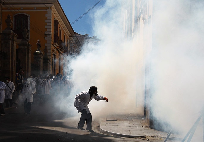 La Paz, Bolivia: A medical student runs from a cloud of teargas fired by police during clashes with students in solidarity with striking public doctors. Public doctors have been on strike for over a month in response to a decree by President Evo Morales, who hoped to extend their professional working hours from six to eight hours per day